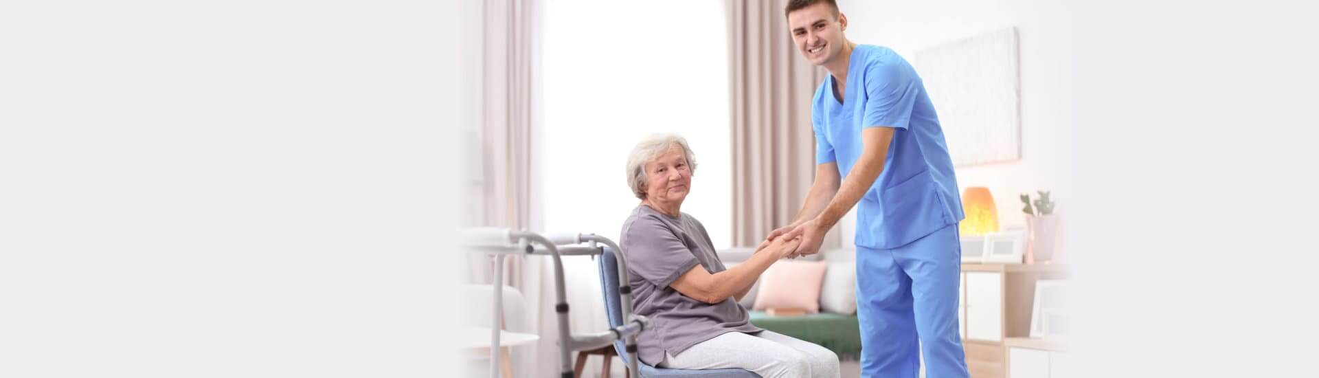 Senior woman walking with assistance of young caregiver